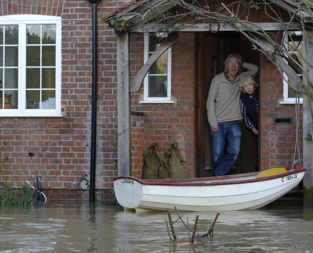 Residents Nigel and Jane Gray look out from their front door after the River Thames flooded the village of Wraysbury, in southern England on Tuesday.