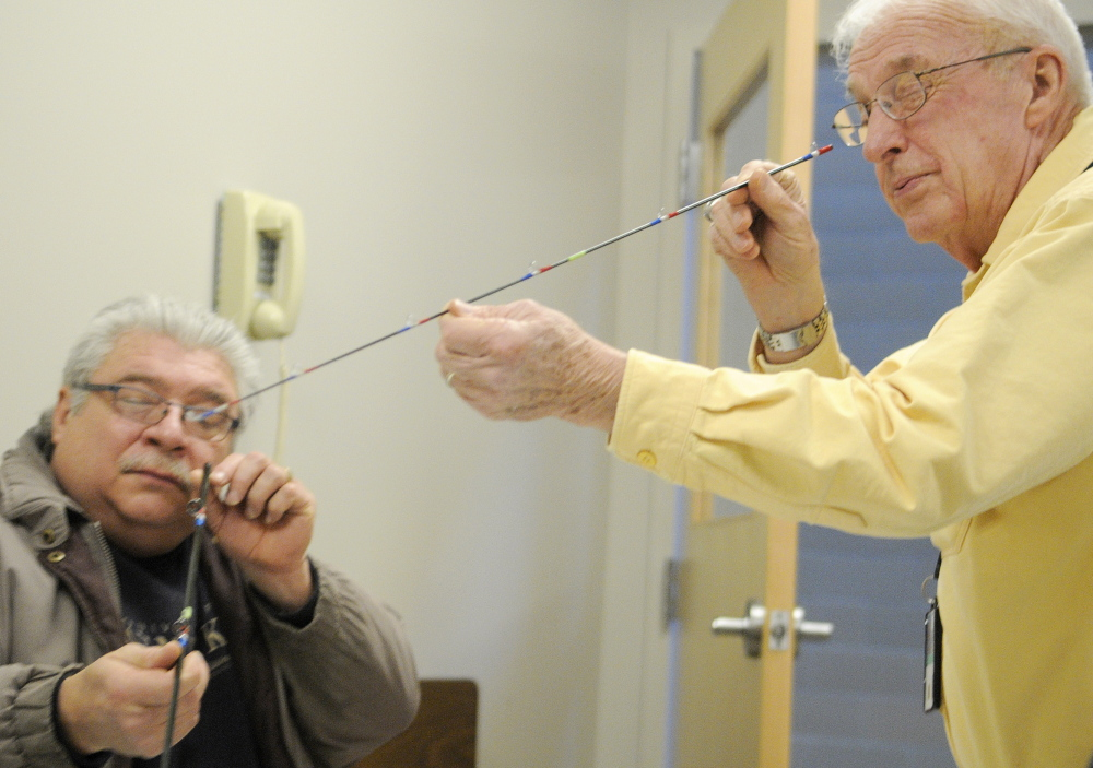 Volunteer Don Taylor, right, inspects a section of a fly rod that veteran Dwaine LaChance assembled Wednesday at VA Maine Healthcare Systems-Togus during a meeting of Project Healing Waters. The program helps disabled service members experience fly-fishing.