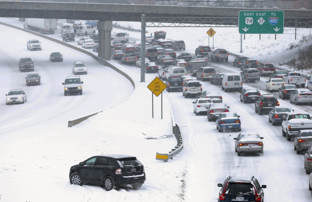 Traffic moves slowly on a freeway leaving downtown Charlotte as snow continues to fall on Tuesday. A fierce winter storm brought heavy snow, freezing rain and a possibly historic accumulation of ice to the southeastern United States.