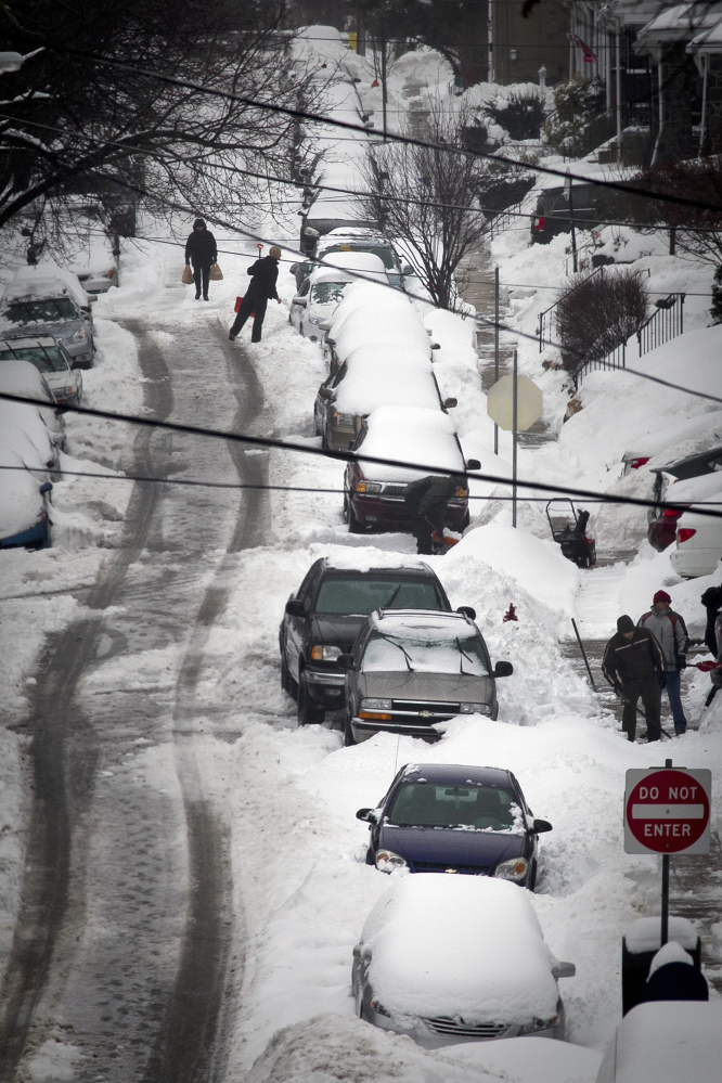 Residents of hilly Monastery Avenue in the Roxborough section of Philadelphia dig out their cars during Thursday's storm.