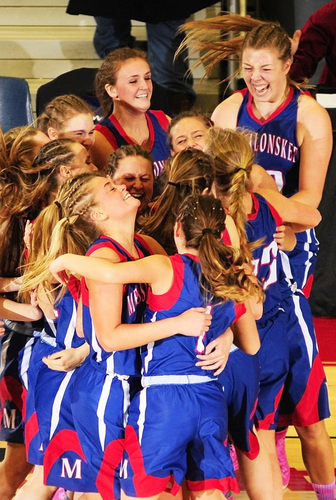 Messalonskee playes celebrate after their 46-42 overtime victory over second-seeded Lawrence in an Eastern Class A girls' basketball quarterfinal Friday at the Augusta Civic Center.