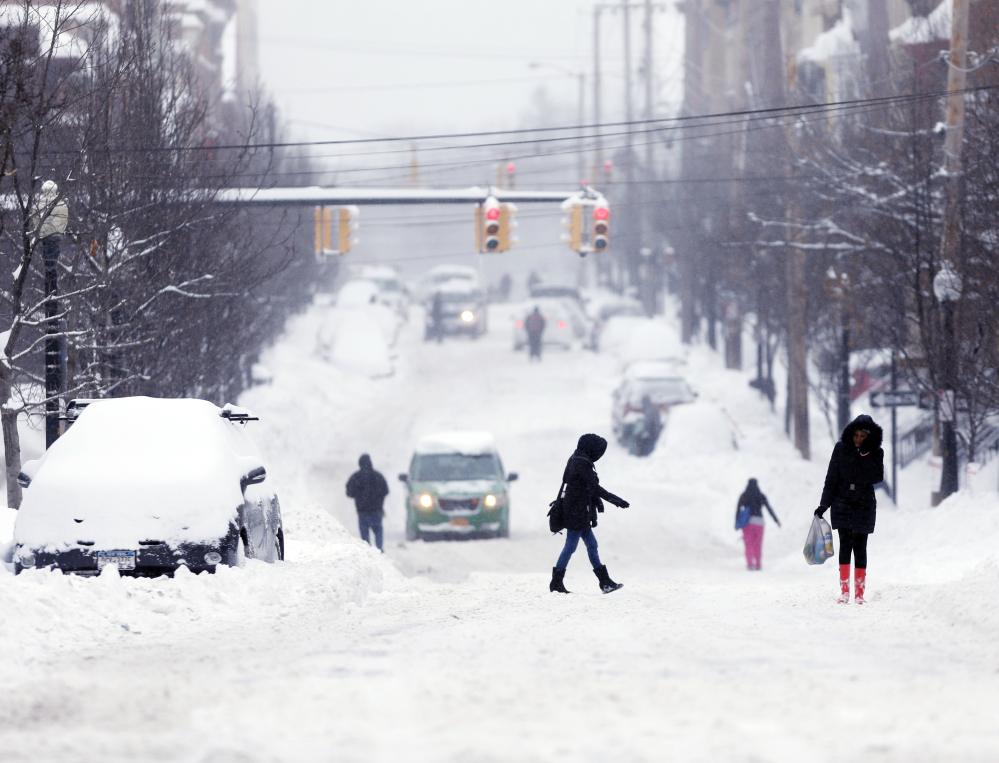 Pedestrians walk along snow-covered Lark Street on Friday in Albany, N.Y.