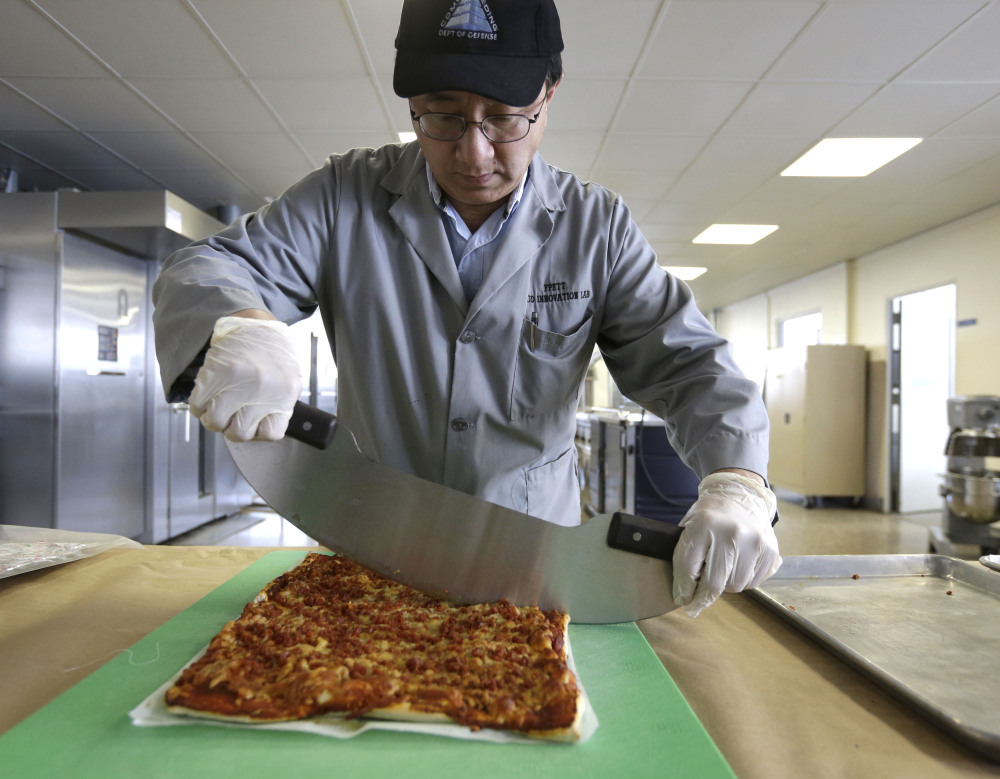 Food technologist Tom Yang cuts a prototype pizza at a U.S. military laboratory in Natick, Mass. Pizza has been one of the most requested meal options of troops in combat zones and disaster areas.
