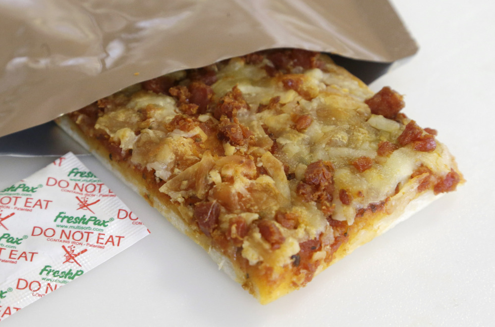 A slice of prototype pizza to be used in individual field rations – known as meals ready to eat, or MREs – sits next to a packet known as an oxygen scavenger at a U.S. military lab in Natick, Mass.