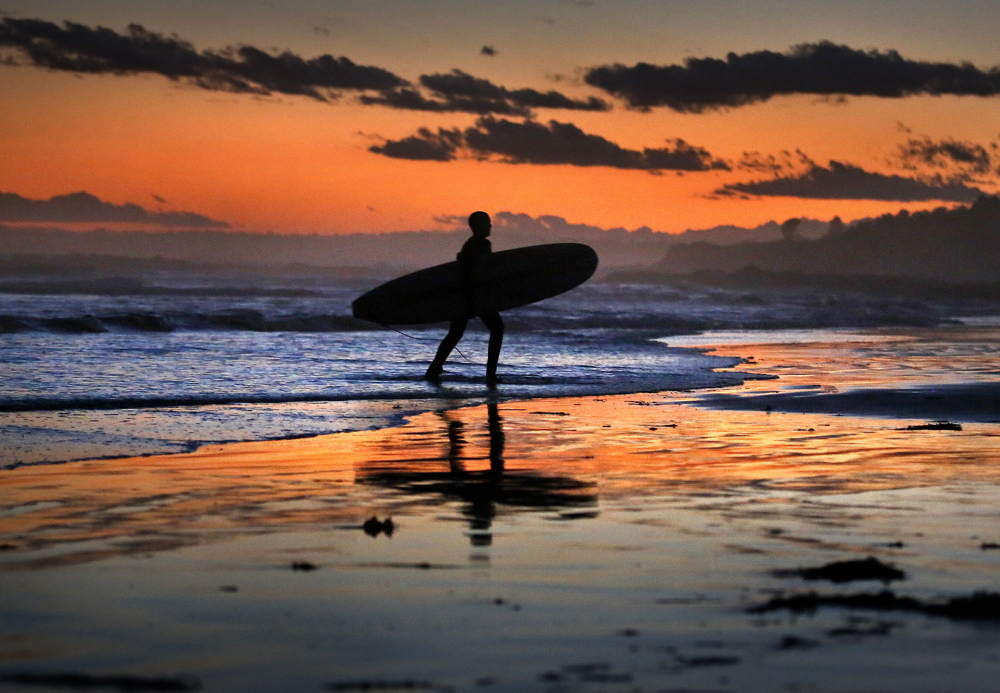 A surfer runs onto Higgins Beach after getting in the water for a late surf session last November. Surfing is one activity that makes Scarborough a happy seaside town.