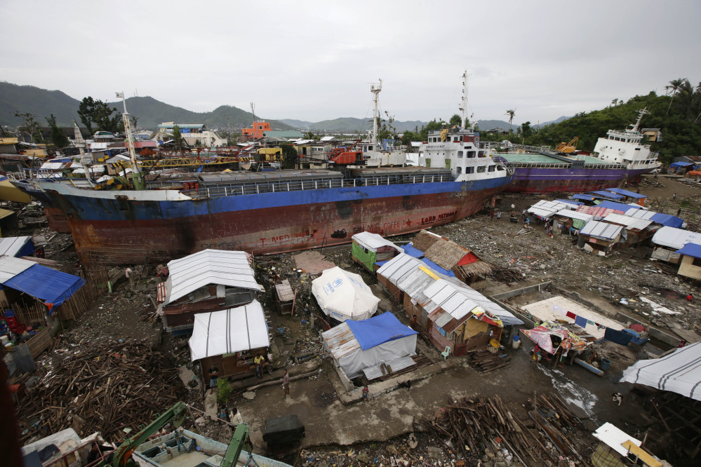 Typhoon survivors continue to live in temporary shelters they built around cargo ships that were washed inland by Typhoon Haiyan in Tacloban city in central Philippines.