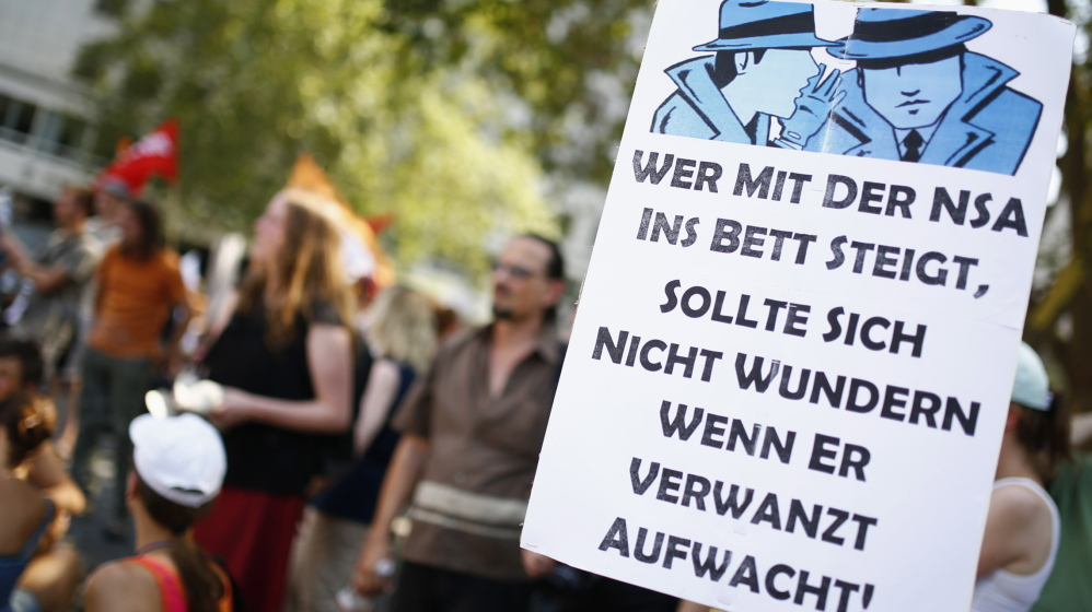 """Protesters are seen behind a placard reading """"Who shares his bed with NSA should not wonder why he wakes up bugged"""" during a demonstration in Frankfurt last July."""