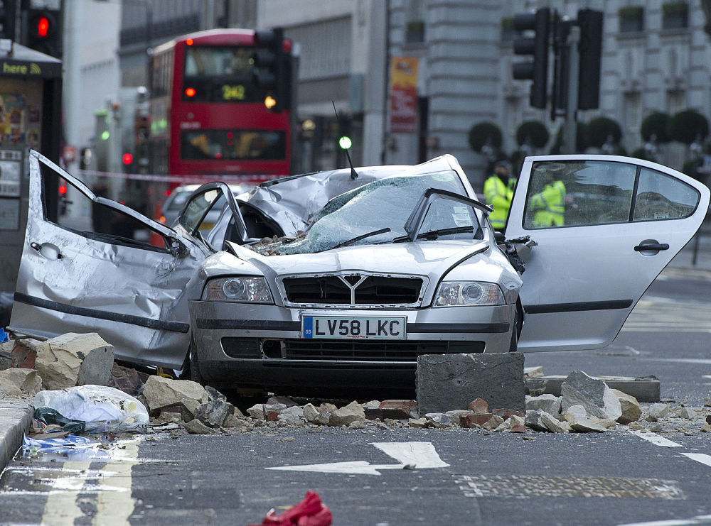 A taxi driver was killed in central London when large chunks of masonry fell from a building on this car. More heavy rain and winds were expected Saturday.