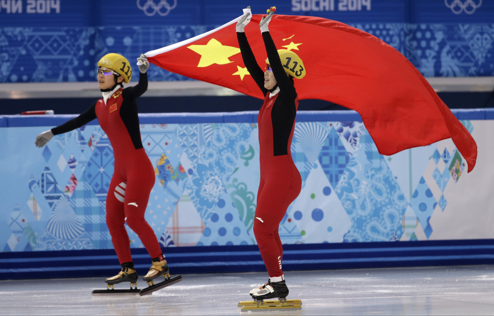 Zhou Yang of China, right, celebrates placing first in a women's 1,500-meter short track speedskating final with Li Jianrou of China, left, at the Iceberg Skating Palace during the 2014 Winter Olympics on Saturday in Sochi, Russia.