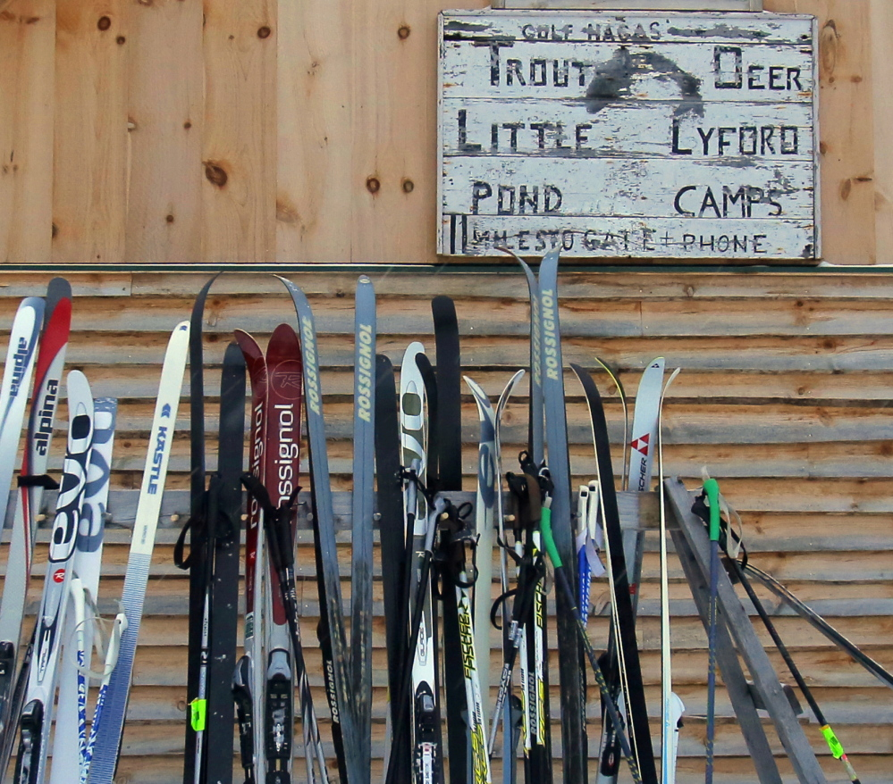 Under an old sign for the Little Lyford Pond Camps, a rack of skis attests to popularity of the camp with outdoor enthusiasts.