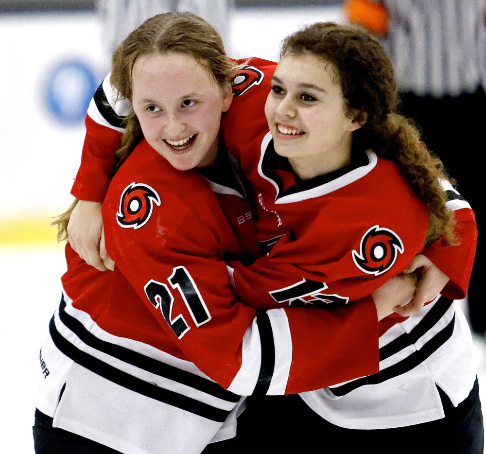 Scarborough's Samantha Shoebottom and Madison O'Reilly embrace after the Red Storm defeated Lewiston 3-1 in the girls' hockey championship in Lewiston on Saturday.