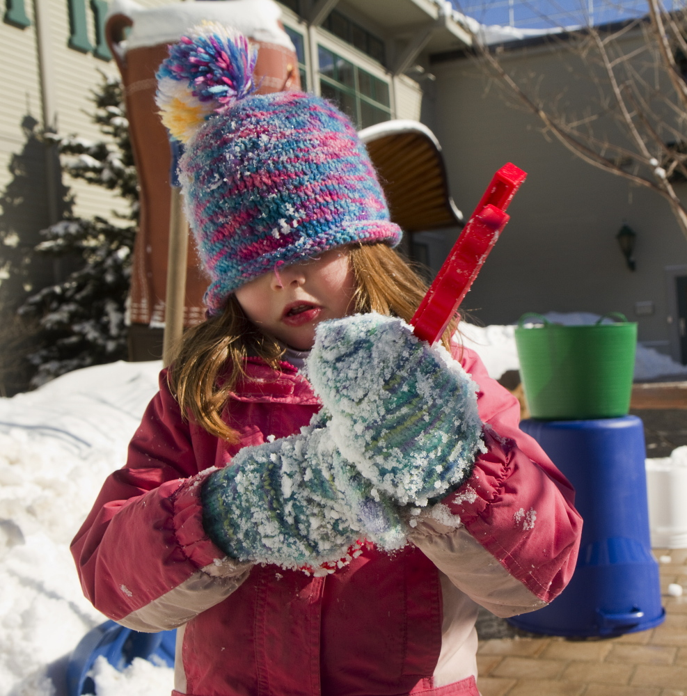 Carl D. Walsh/Staff Photograph3er Phoebe Kibler, 6 of Topsham, makes a snowball while participating in snow sculpture activities outside LL Bean in Freeport on Sunday, February 16, 2014.