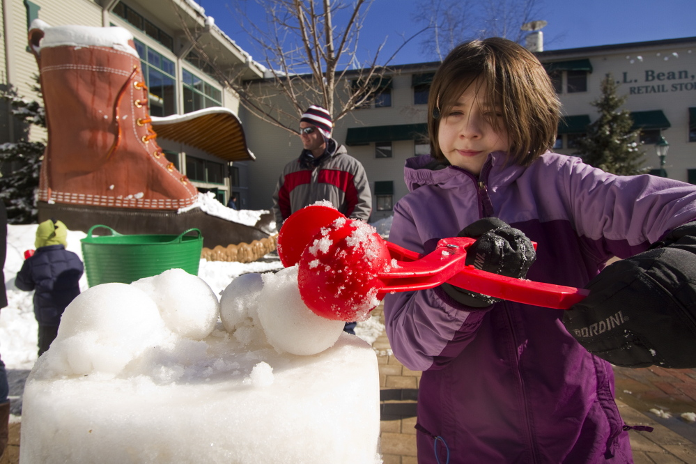 Catie Cataldo, 10, of Acton, Mass., carefully places a snowball atop a snow sculpture she was making.