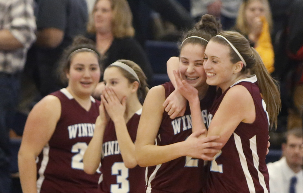 Sam Frost, right, and Luisa Sbardella hug after Windham beat Thornton Academy 34-32 in a Western Class A girls' basketball quarterfinal Monday at the Portland Expo.