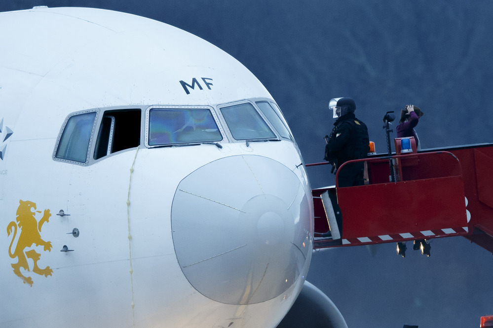 Police stand on the stairs after passengers were evacuated from a hijacked Ethiopian Airlines Plane on the airport in Geneva, Switzerland, on Monday.