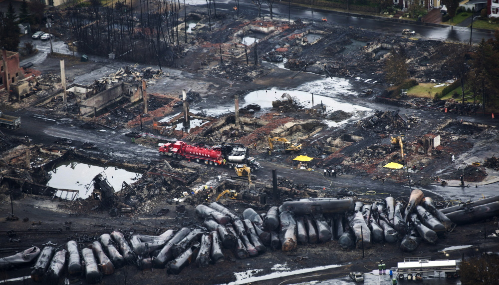 2013 Associated Press File Photo Workers comb through debris after an oil train derailed and exploded in the town of Lac-Megantic, Quebec, last July, killing 47 people. More trains are being used to ship oil, and they travel through populated areas.