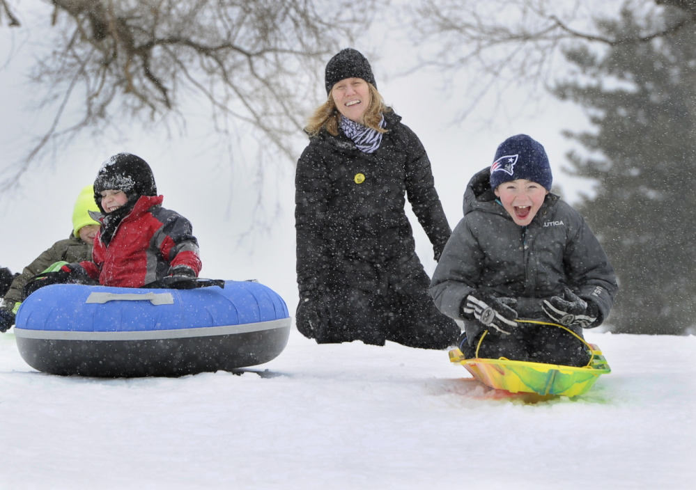 Paula Blake of Falmouth pushes her son Ethan Doucette, 6, right, down a steep slope at Maine Audubon in Falmouth as friends Noah Herdrich, 7, and Cayden Jaynes, 6, left, also of Falmouth, join in Tuesday at the start of the latest snowstorm to hit southern Maine.