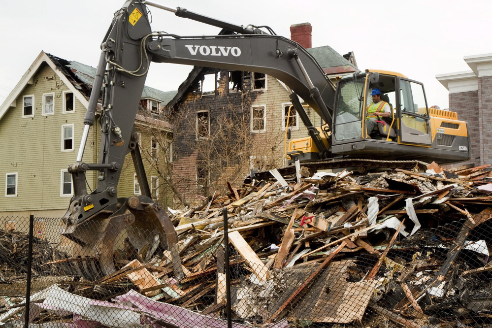 A demolition crew member cleans up the rubble from the Blake Street fire in Lewiston in May.
