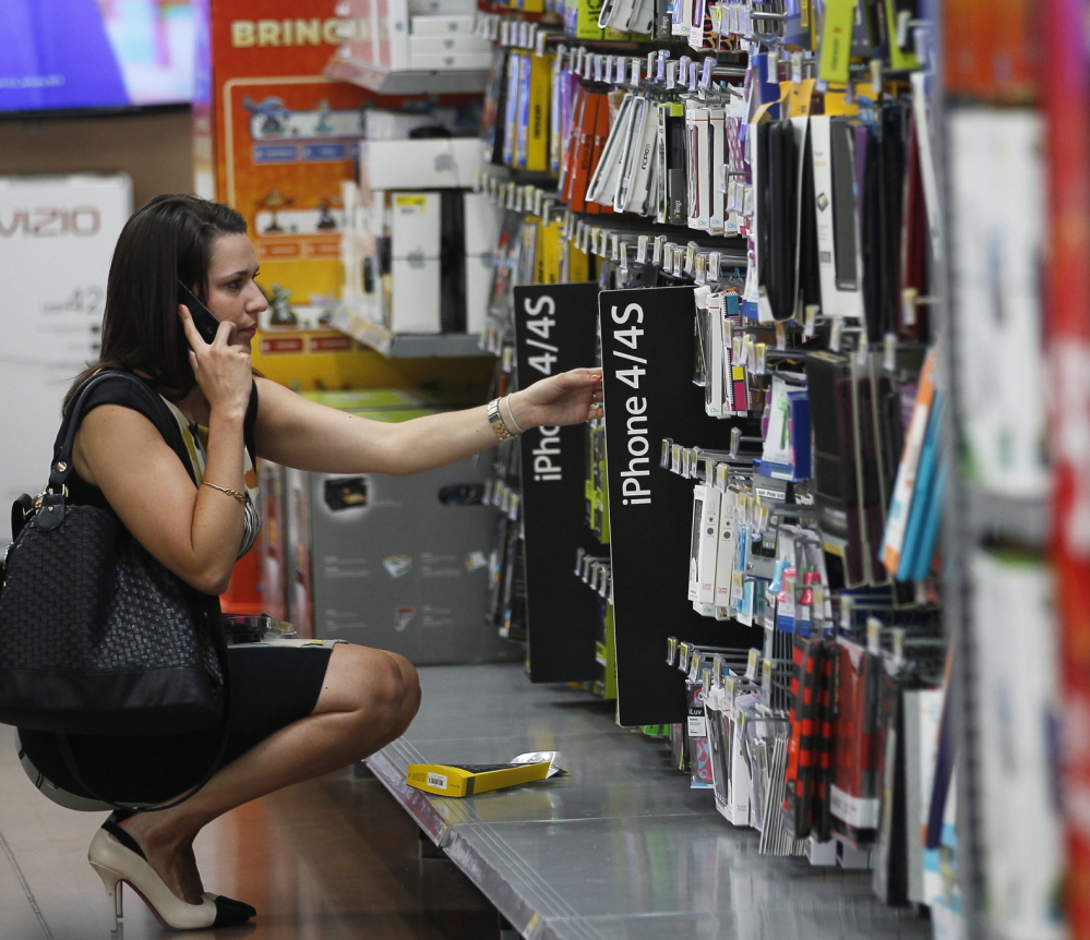 A woman shops while talking on her cellphone. The FTC held a workshop Wednesday on the issue of retailers using mobile-based technology to track shopper's movements.