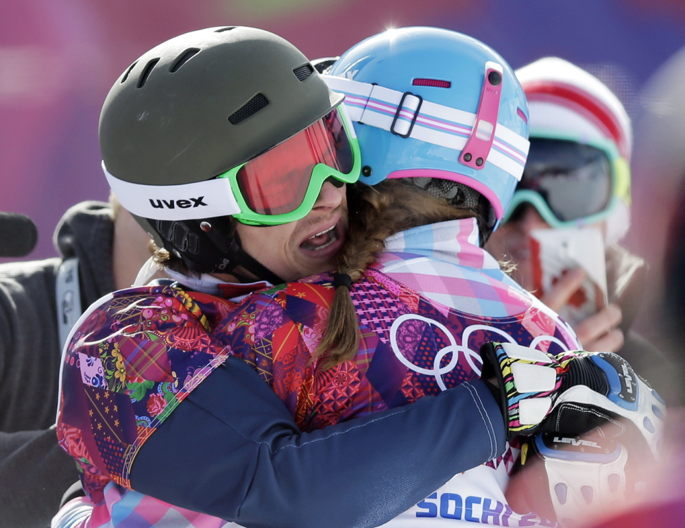 Russia's Vic Wild, left, celebrates after winning the gold medal in the men's snowboard parallel giant slalom final, with his wife and bronze medalist in the women's snowboard parallel giant slalom final, Russia's Alena Zavarzina, at the Rosa Khutor Extreme Park, at the 2014 Winter Olympics.