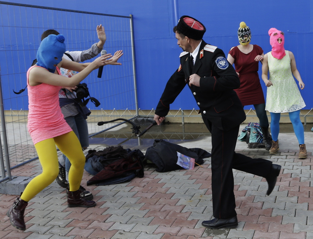 A Cossack militiaman attacks Nadezhda Tolokonnikova and a photographer as she and fellow members of the punk group Pussy Riot stage a protest performance Wednesday. The group had gathered in a downtown Sochi restaurant, about 21 miles from where the Winter Olympics are being held. They ran out of the restaurant wearing brightly colored clothes and ski masks and were set upon by about a dozen Cossacks, who are used by police authorities in Russia to patrol the streets.