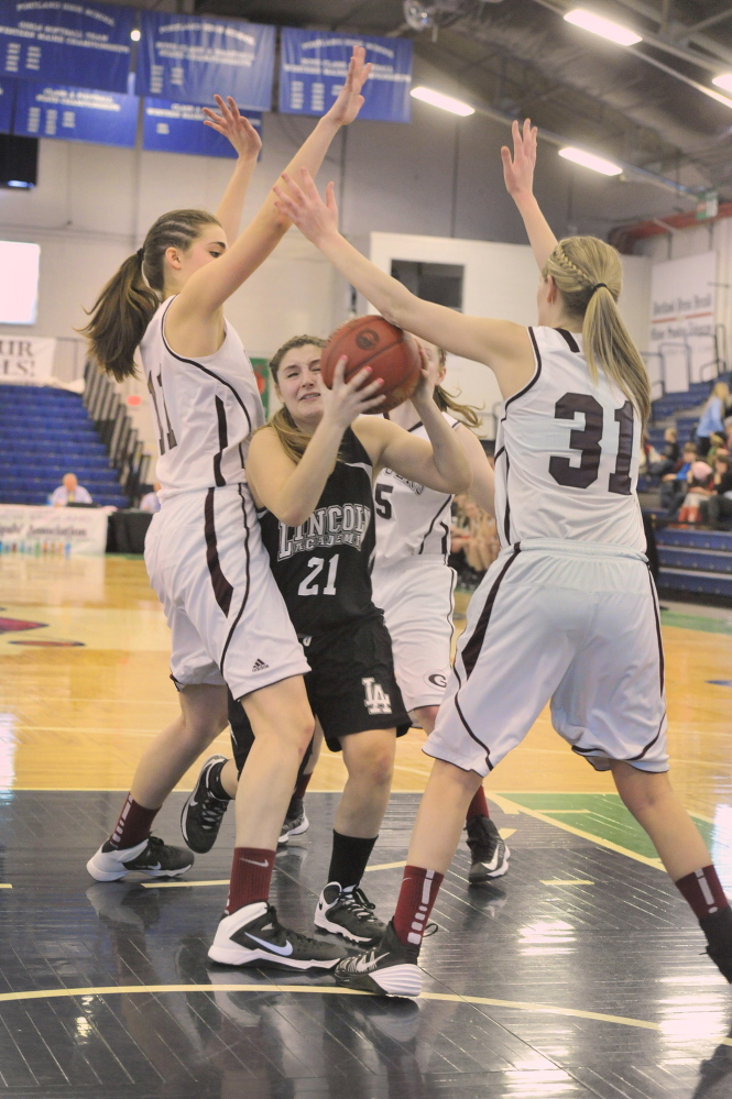 Taylor Oliver of Lincoln Academy tries to find an opening between Greely's Ashley Storey, left, and Madison Cyr during their Western Class B girls' basketball quarterfinal Wednesday at the Portland Expo. Greely advanced with a 55-27 victory.