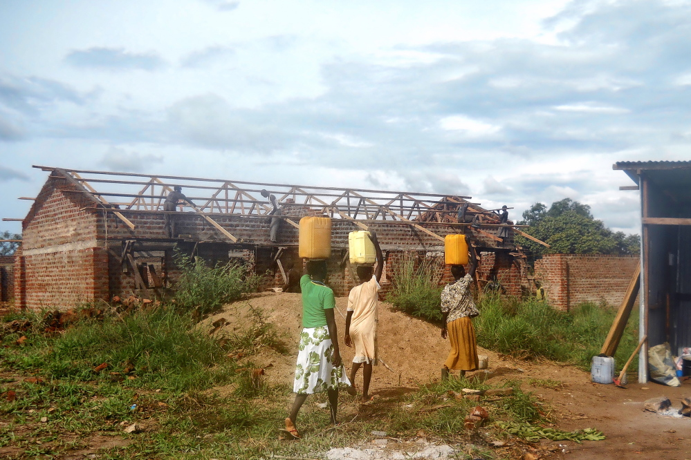 Volunteers carry water to be used in building the Nylo Hope Primary School in South Sudan in this undated photo. The Portland-based non-profit group Aserala is raising funds for the school construction. About 350 students are now studying in the school, which is half complete.
