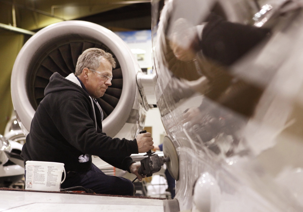Ron Tardiff buffs a Hawker 9000 airplane at Mac Air Group in Portland. The former Maine Aviation Corp. has shuttered its flight school and charter business and is focusing on the high-end aviation market.