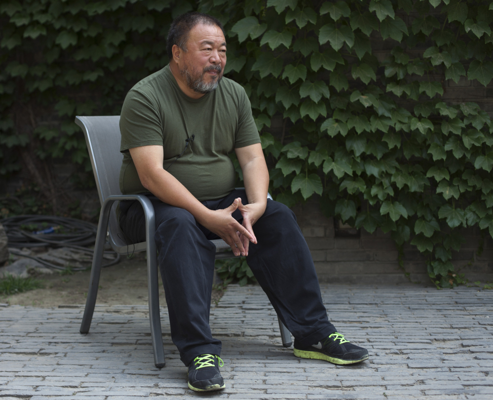 FILE - In this May 22, 2013 file photo, artist Ai Weiwei speaks to journalists at the courtyard of his studio in Beijing. Ai, who helped make his name smashing a valuable vase in the name of art, said Wednesday, Feb. 19, 2014 that he was miffed about another artist destroying one of his vases in Florida. Maximo Caminero was charged with criminal mischief after destroying a vase valued at $1 million that was part of Ai's exhibit at the Perez Art Museum Miami. The Florida artist said he smashed the vase Sunday, Feb. 16 to protest the institution's lack of displays of local artists. Ai said Wednesday that he did not agree with Caminero's tactic. (AP Photo/Alexander F. Yuan, File)
