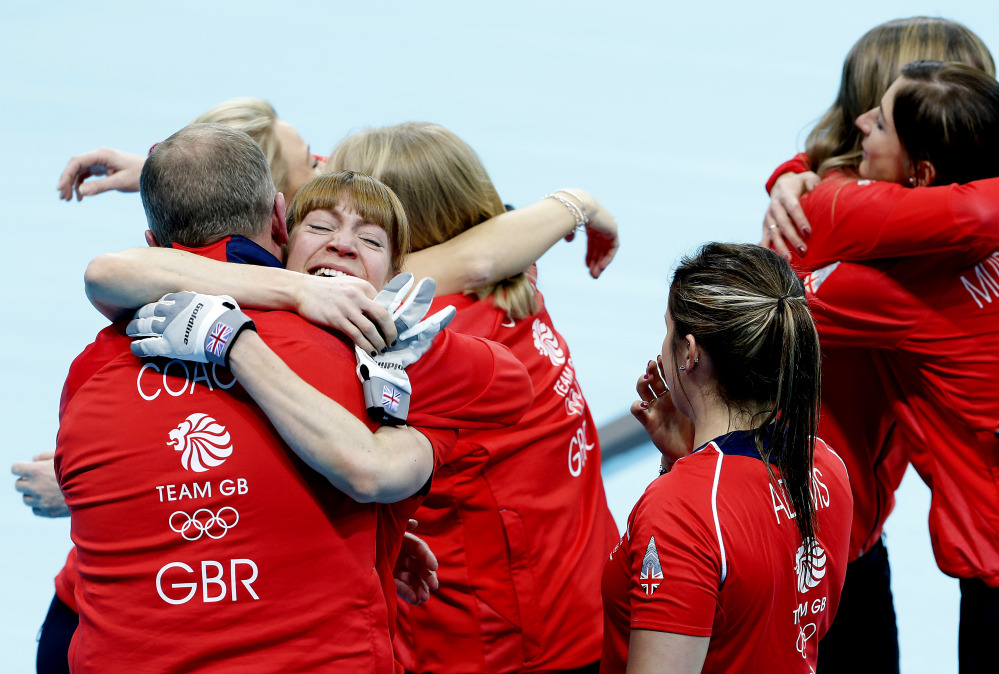 Britain's Claire Hamilton hugs her coach as her team celebrates after beating Switzerland in the women's curling bronze medal game at the 2014 Winter Olympics, Thursday, Feb. 20, 2014, in Sochi, Russia.
