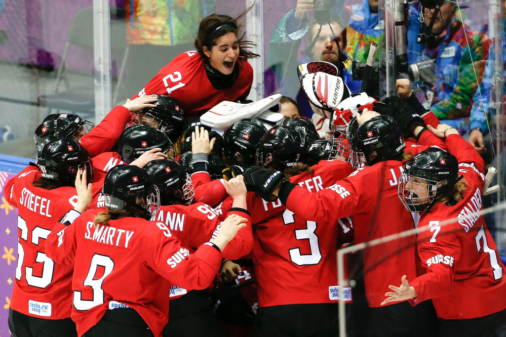 Team Switzerland celebrates their 4-3 win over Sweden in the women's bronze medal ice hockey game at the 2014 Winter Olympics, Thursday, Feb. 20, 2014, in Sochi, Russia.