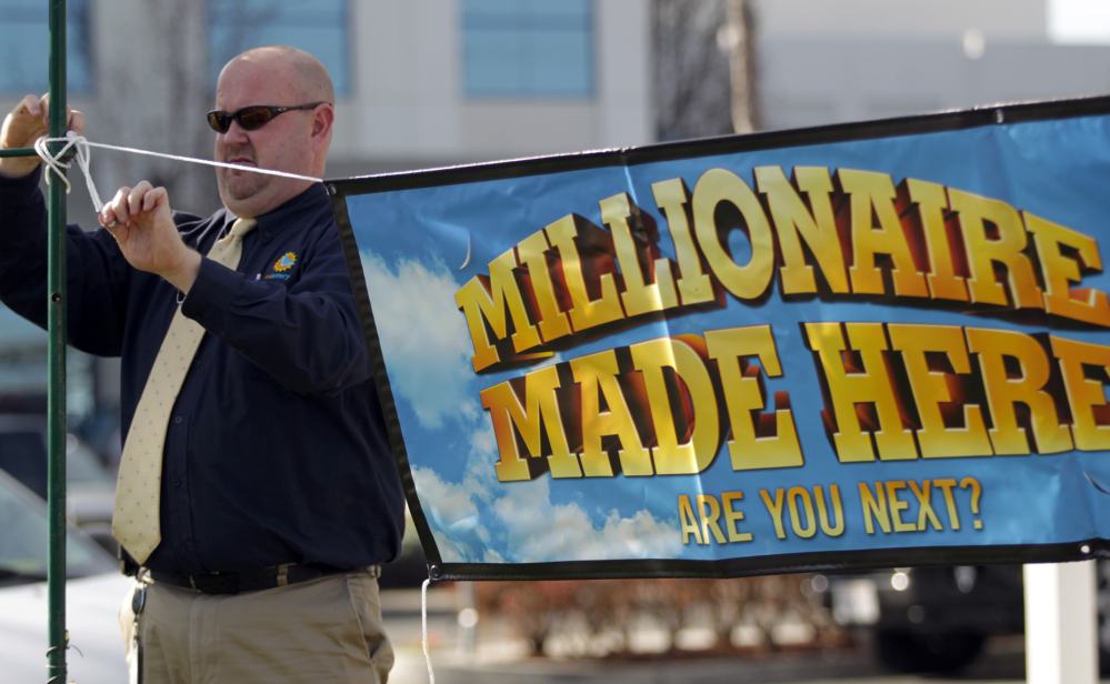 "California Lottery official John Reading hangs a ""Millionaire Made Here"" sign at the Dixon Landing Chevron that sold a winning $425 million Powerball ticket in Milpitas, Calif. The owners of the station received a $1 million bonus for selling the ticket."