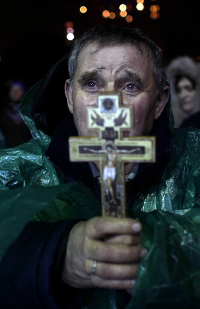 An anti-government protester holds a crucifix as he prays at Independence Square in Kiev, Ukraine, Thursday.