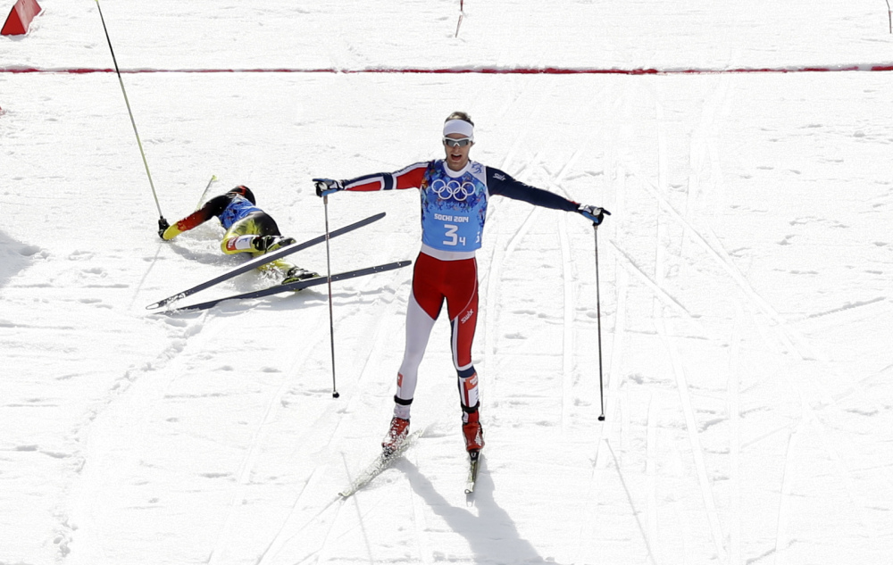Norway's Joergen Graabak celebrates winning the gold as Germany's silver medal winner Fabian Riessle, left, falls into the snow after crossing the finish line of the cross-country portion of the Nordic combined Gundersen large hill team competition at the 2014 Winter Olympics, Thursday, Feb. 20, 2014, in Krasnaya Polyana, Russia.