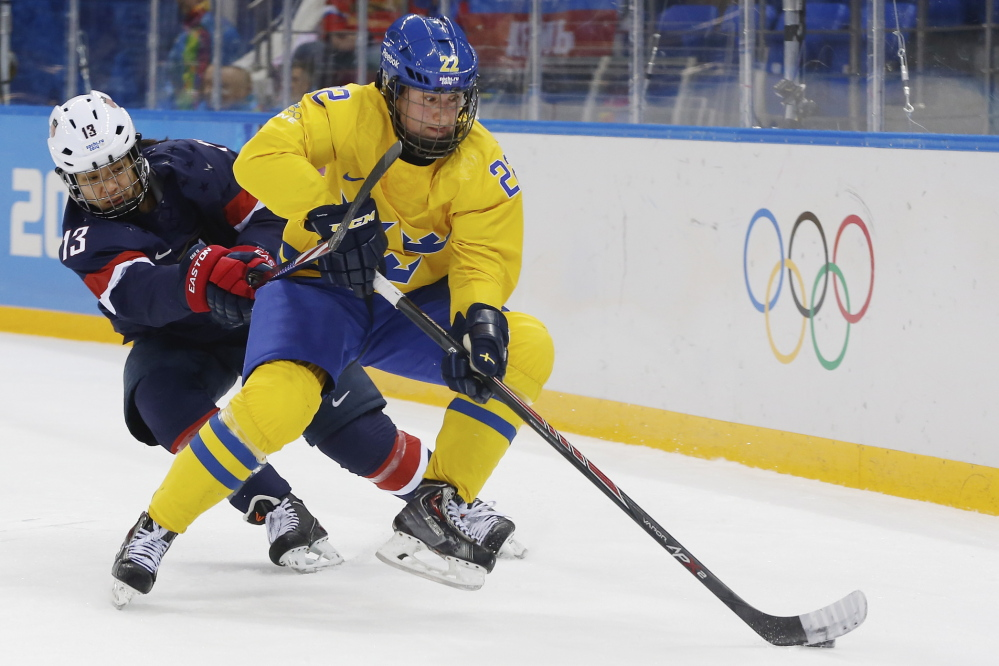 Emma Eliasson of Sweden takes control of th e puck away from Julie Chu of the United States during the first period of the 2014 Winter Olympics women's semifinal ice hockey game. Chu has been selected to carry the American flag at the closing ceremonies.