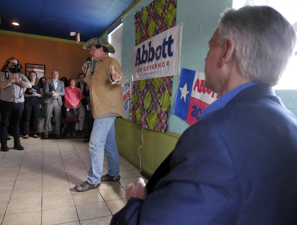 Rocker Ted Nugent, left, introduces Texas gubernatorial candidate Greg Abbott, Tuesday during a stop in Denton, Texas, to promote early voting. Wendy Davis is the Democratic opponent.