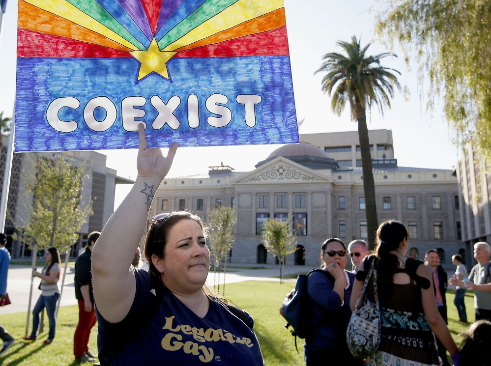 Jo Beaudry holds up a sign as she joins gay rights supporters protesting in Phoenix a bill that passed the Arizona Legislature that would allow businesses to refuse service to gays on religious grounds.