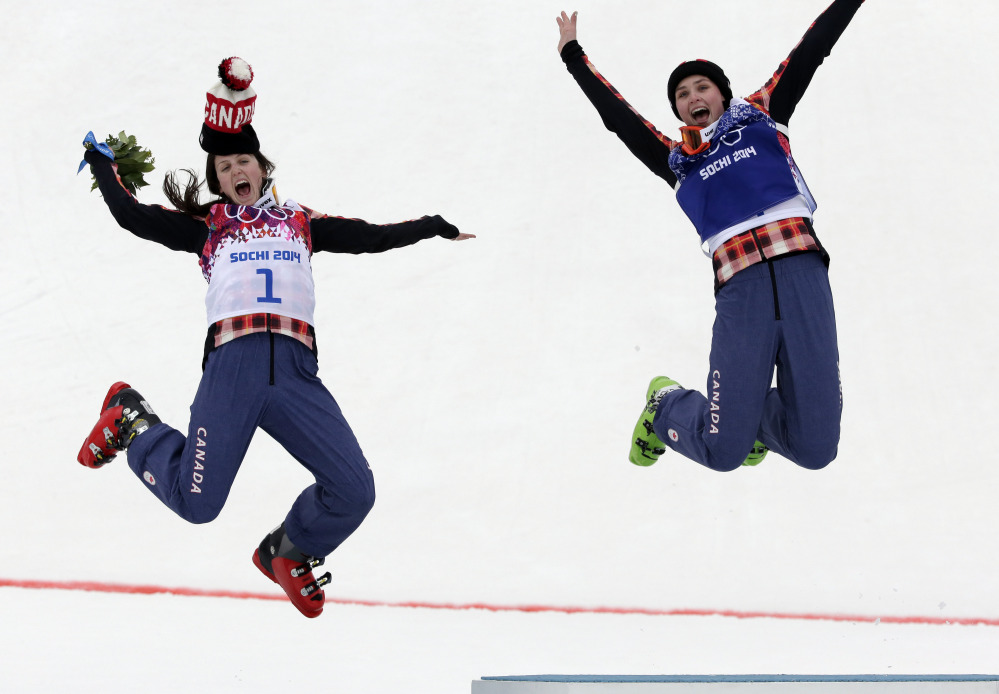 Women's ski cross gold medalist Marielle Thompson of Canada, right, celebrates Friday on the podium with silver medalist and compatriot Kelsey Serwa at the 2014 Winter Olympics in Krasnaya Polyana, Russia.