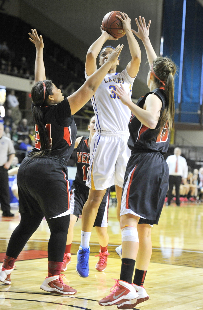 Tiana-Jo Carter of Lake Region shoots over Jordan Agger, left, and Nicole Moody of Wells during the Western Class B girls' basketball championship game Saturday at the Cumberland County Civic Center. Carter had 24 points and 15 rebounds to lead Lake Region to a 59-51 win.