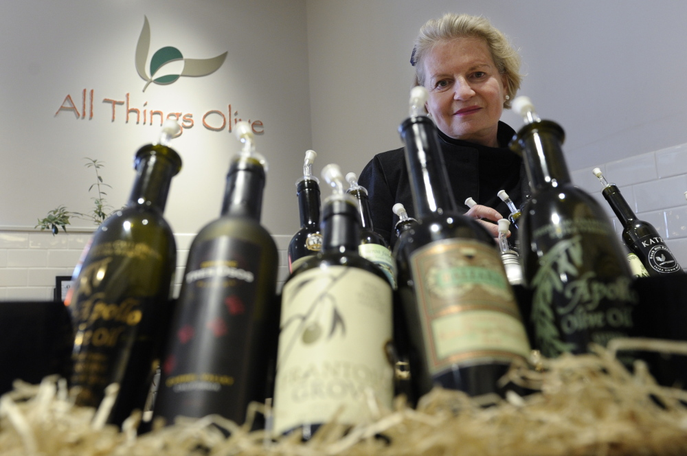 "Patricia Darragh, executive director of the California Olive Oil Council, shows off a collection of California olive oil. In another decade or two, Americans may be more familiar with the domestic variety. ""We're where the California wine industry was 20 or 30 years ago,"" she says."