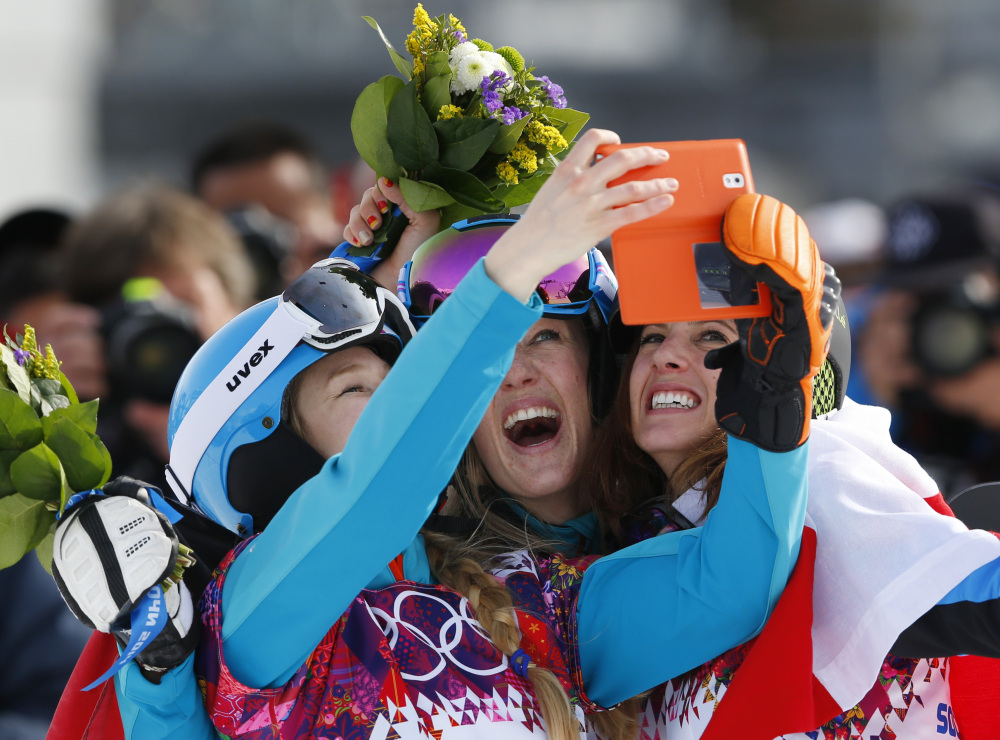 Women's snowboard parallel slalom medalists, from left to right, bronze medalist Amelie Kober of Germany, silver medalist Anke Karstens of Germany center, and gold medalist Julia Dujmovits of Austria take photos of themselves during a flower ceremony at the Rosa Khutor Extreme Park at the 2014 Winter Olympics on Saturday in Krasnaya Polyana, Russia.