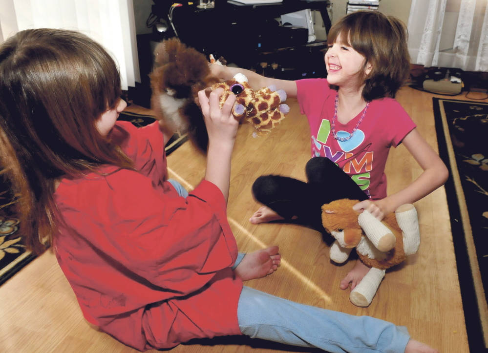 Kaitlyn Parker, right, and her sister Briana play with toys Wednesday at their home in Augusta. Kaitlyn is dealing with a medical condition known as Marfan syndrome, a genetic disorder that can affect ligaments and the heart.