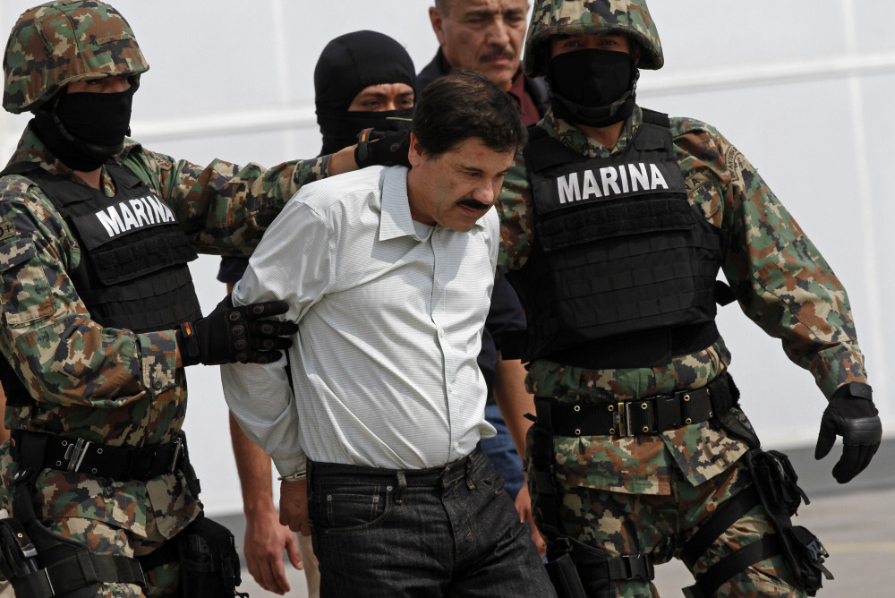 """Joaquin """"El Chapo"""" Guzman is escorted to a helicopter in handcuffs by Mexican navy marines at a navy hanger in Mexico City, Saturday."""