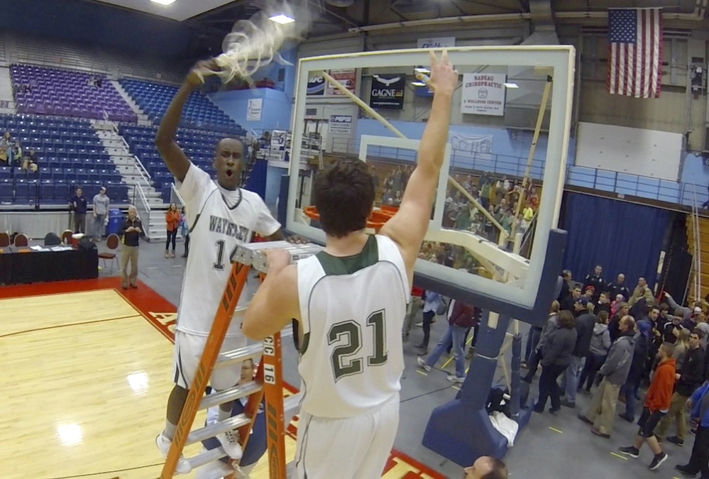 Wayneflete's Serge Nyirikamba, left, and Henry Cleaves cut down one of the nets after the Flyers won the Western Class C boys' basketball championship with a 62-38 win Saturday at the Augusta Civic Center.