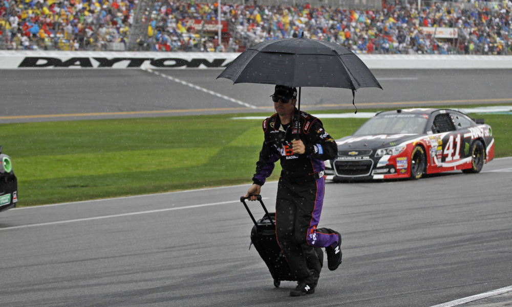 A crew member runs down pit road during a rain delay in the NASCAR Daytona 500 Sunday at Daytona Beach, Fla. The race was stopped after 38 laps.