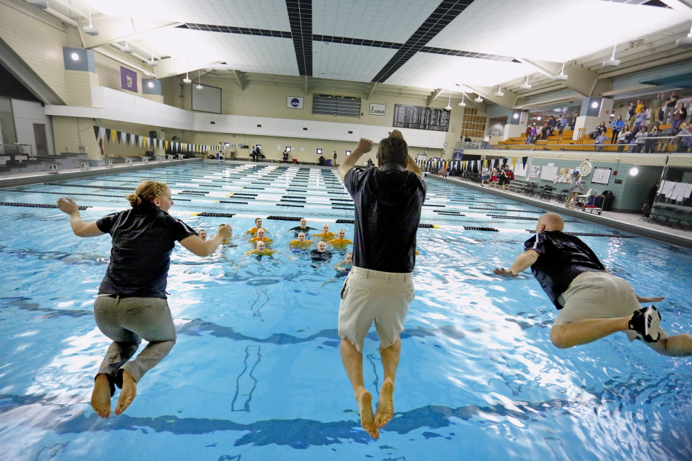 Greely assistant coaches Alisha Copp, left, and Doug Pride, center, and head coach Rob Hale jump into the pool at Bowdoin College in Brunswick Tuesday after the Rangers captured the state championship at the Class B boys' swim meet.