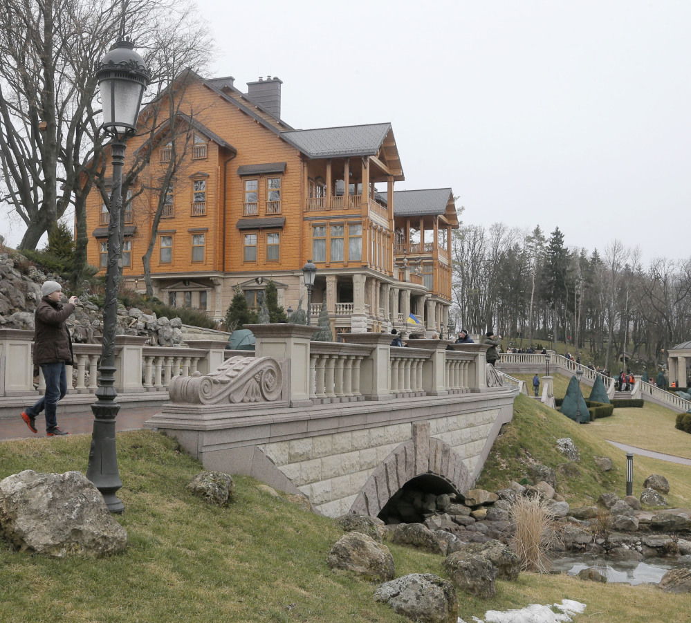 A man takes a photo on the grounds of Ukrainian President Yanukovych's country residence in Mezhyhirya.
