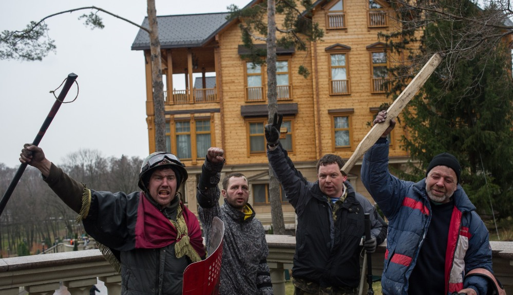 Protesters pose in front of the Ukrainian President Yanukovych's countryside residence in Mezhyhirya, Kiev's region, Ukraine, Saturday. Ukrainian security and volunteers from among Independence Square protesters have joined forces to protect the presidential countryside retreat from vandalism and looting.