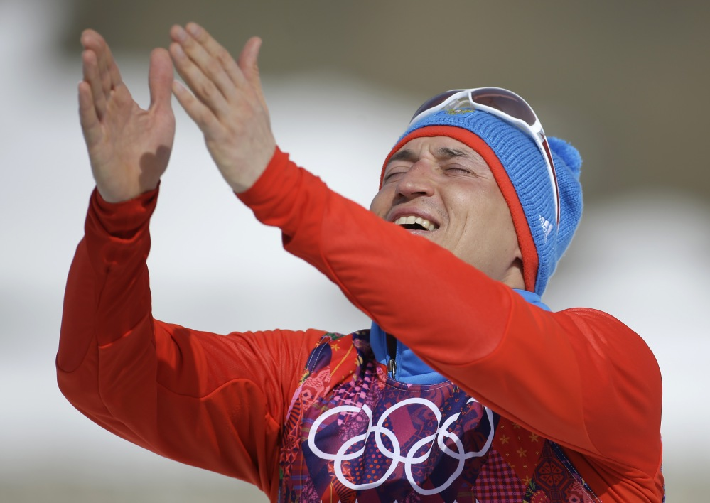 Russia's gold-medal winner Alexander Legkov gestures to the crowd during the flower ceremony of the men's 50K cross-country race Sunday at the 2014 Winter Olympics in Krasnaya Polyana, Russia.