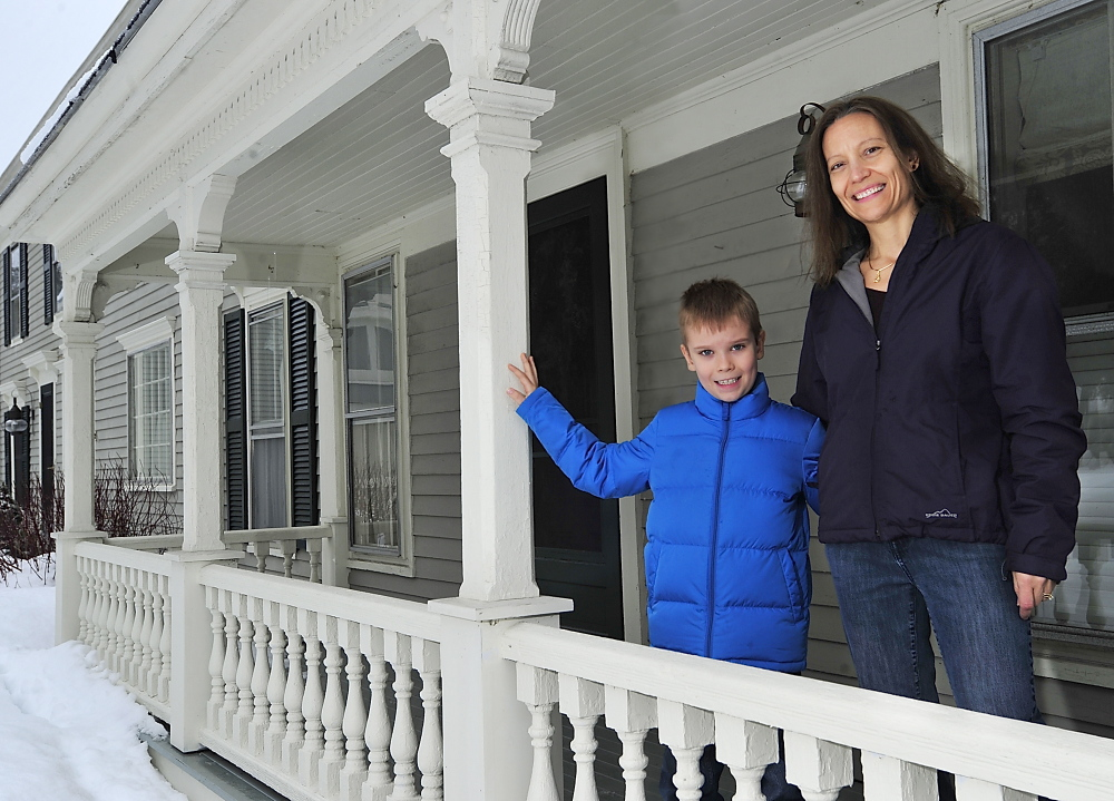 Susan Smith with her son Ethan, 7, at their farmhouse in Cumberland Center. The Smiths, who recently moved from Illinois, were among the first to sign up for natural gas when it becomes available in Cumberland Center.
